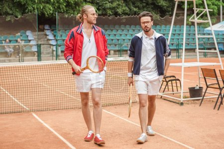 friends with wooden rackets walking on tennis court