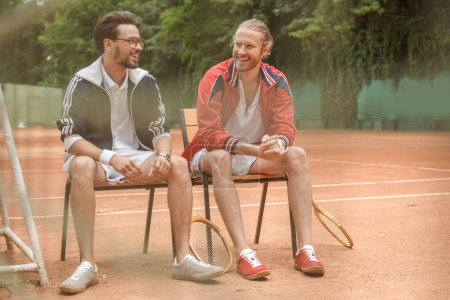 happy sportive friends with wooden rackets sitting on chairs on tennis court