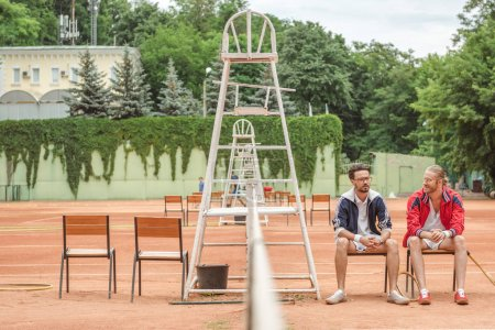 athletic friends with wooden rackets sitting on chairs on tennis court
