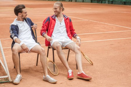 happy friends with wooden rackets sitting on chairs on tennis court