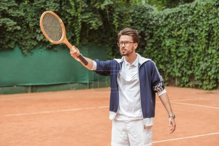 handsome tennis player pointing with wooden racket on tennis court