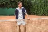 handsome tennis player with racket standing at net on tennis court