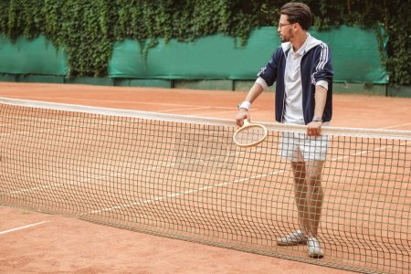 athletic tennis player with wooden racket leaning on tennis net on court