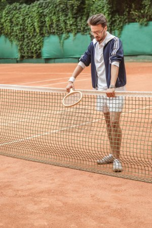 handsome retro sportsman with racket leaning on tennis net on brown court