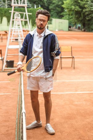 handsome old-fashioned tennis player with racket on brown court near tennis net