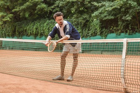 handsome tennis player with racket leaning on tennis net on brown court