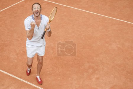 handsome emotional winner with racket yelling and celebrating on tennis court