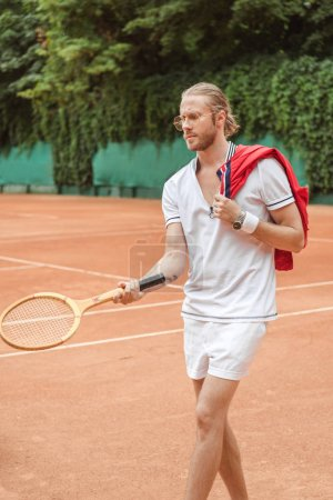 handsome tennis player with retro wooden racket on court