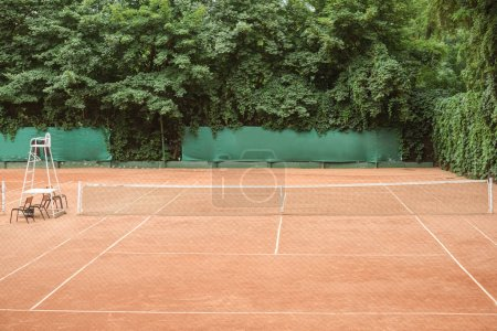 view of brown tennis court with chairs and tennis net