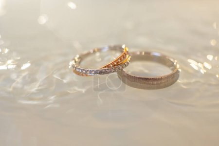 Photo for Close-up of two wedding rings in the water. Beautiful wedding background. - Royalty Free Image