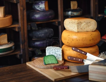 blue cheese, whole cheese head, pyramid of cheeses, Roquefort, Bleu de Coss, Gorgonzola knives