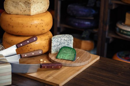 Cheese heads with slices and knives lie on a wooden board with an interior.