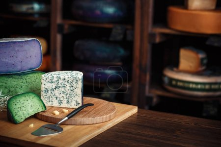 Cheese heads with slices and knives lie on a wooden board with an interior