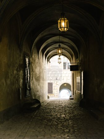 Narrow dark street illuminated by street lamps. Stone pavement in the old town Cesky Krumlov, Czech Republic