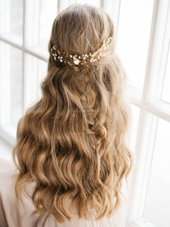 Portrait with natural light of pretty young woman with beautiful hairstyle decorated by stylish gold hair accessory, rear view