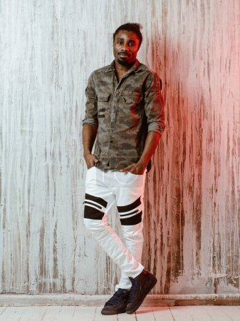 Young African-American male standing near wall in hip-hop style clothes and looking at camera