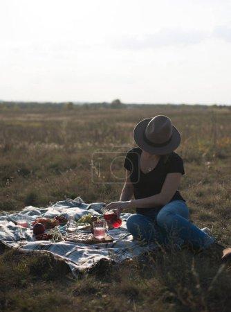 Photo pour Jolie jeune femme au chapeau marron assise sur une couverture et profitant d'un pique-nique dans un champ ensoleillé d'automne - image libre de droit