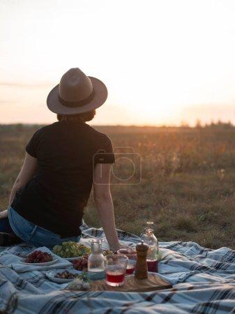 Photo pour Jolie jeune femme au chapeau marron assise sur une couverture et profitant d'un pique-nique dans le champ d'automne au coucher du soleil - image libre de droit