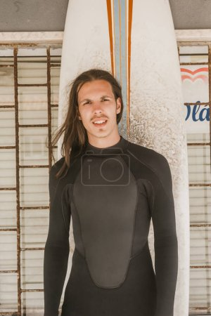 portrait of man with long hair in wetsuit with surfing board looking at camera
