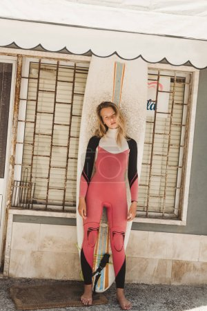 young woman in wetsuit with surfing board standing against building wall in Portugal