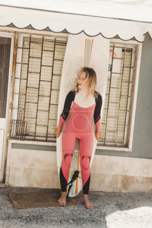 cheerful woman in wetsuit with surfing board standing against building wall in Portugal