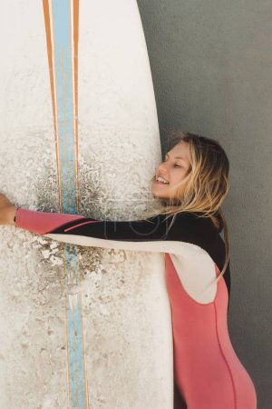 portrait of smiling woman in wetsuit hugging surfing board against grey wall