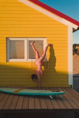 young woman in pink bikini standing on hands against yellow building with surfing board near by in Portugal