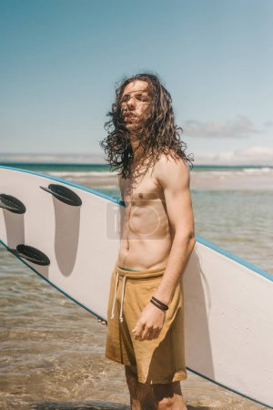 portrait of young man with surfboard standing in ocean on summer day