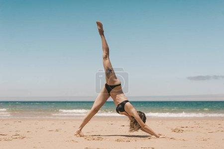 Photo pour Vue de côté de femme pratiquant à la baisse face à pose d'yoga de chien sur la plage de sable fin - image libre de droit