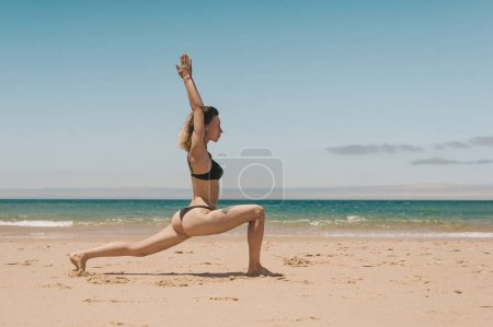 side view of young woman in black bikini standing in Warrior yoga position on sandy beach