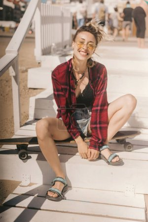 young smiling woman in sunglasses and shirt resting on longboard on wooden stairs on beach