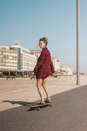 young woman in sunglasses and shirt skating on longboard on street in Portugal