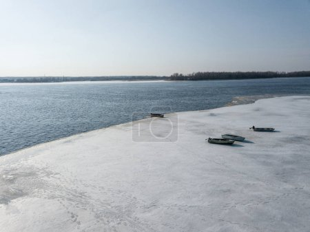 aerial view of scenic river bank with boats covered with snow, Kyiv, Ukraine