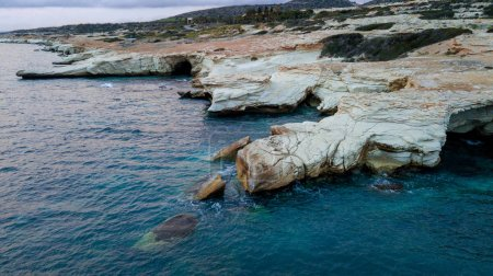 aerial view of white rocks on seashore with blue water, Cyprus