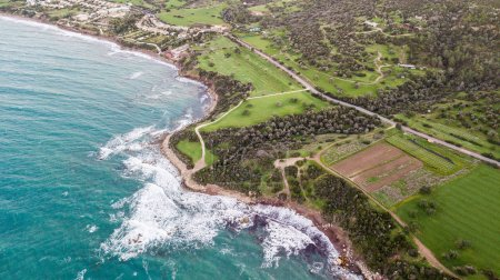 aerial view of foamy waves crashing on seashore with green grass and trees, Israel