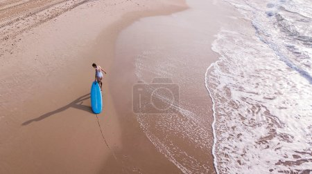 Photo for Aerial view of woman in white swimsuit pulling surfboard on sandy beach, Ashdod, Israel - Royalty Free Image