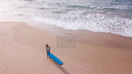 Photo for Aerial view of young woman in swimsuit with surfboard on sandy beach, Ashdod, Israel - Royalty Free Image