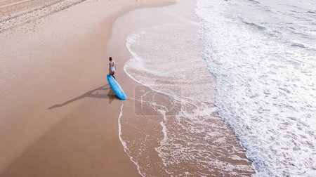 aerial view of young woman in swimsuit pulling surfboard on sandy beach, Ashdod, Israel