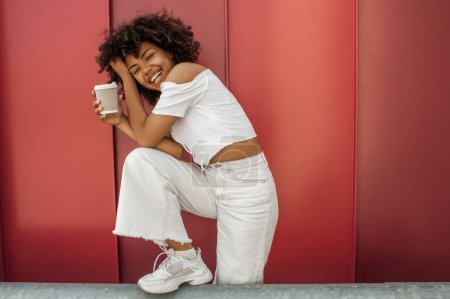 happy african american girl holding disposable coffee cup and laughing on street