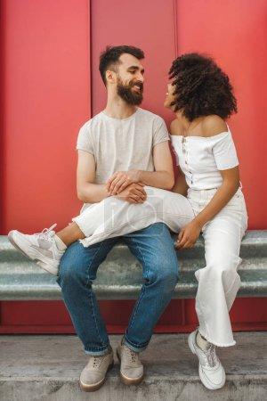 Beau couple interracial jeune heureux souriant mutuellement tout en étant assis ensemble sur la rue