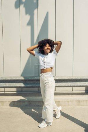 Photo pour Belle femme afro-américaine de jeune heureuse, rire avec les mains derrière la tête sur la rue - image libre de droit