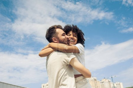 Photo for Low angle view of happy young multiracial couple hugging against blue sky - Royalty Free Image
