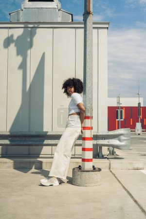 side view of beautiful stylish young african american woman leaning at pole on street