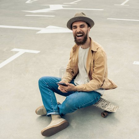 happy bearded man sitting on skateboard and using smartphone