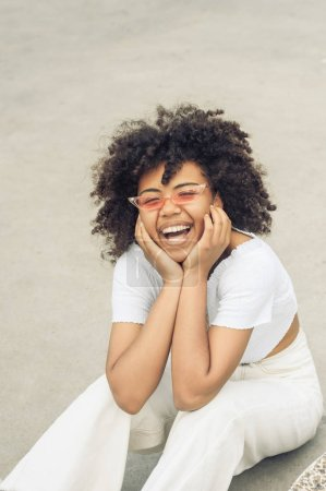 high angle view of happy young african american woman in sunglasses sitting and laughing on street