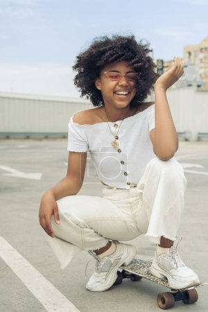 Photo for Happy young african american woman crouching on skateboard and laughing on street - Royalty Free Image