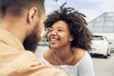 beautiful happy young multiracial couple laughing together on street