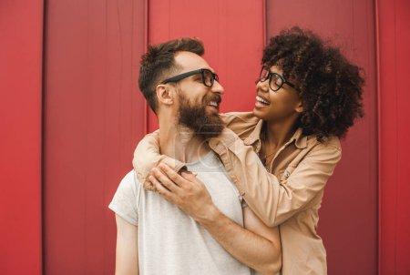 Photo pour Heureux les jeunes interracial couple dans lunettes câlins et sourire l 'autre - image libre de droit