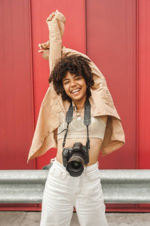 Photo for Cheerful african american girl with camera raising hands on street - Royalty Free Image