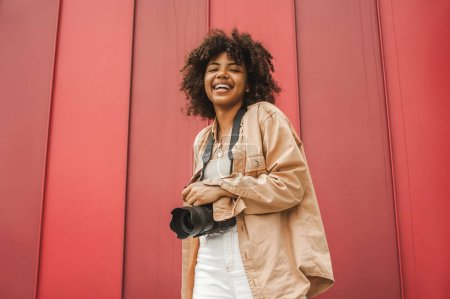 low angle view of cheerful young african american woman holding camera and smiling at camera